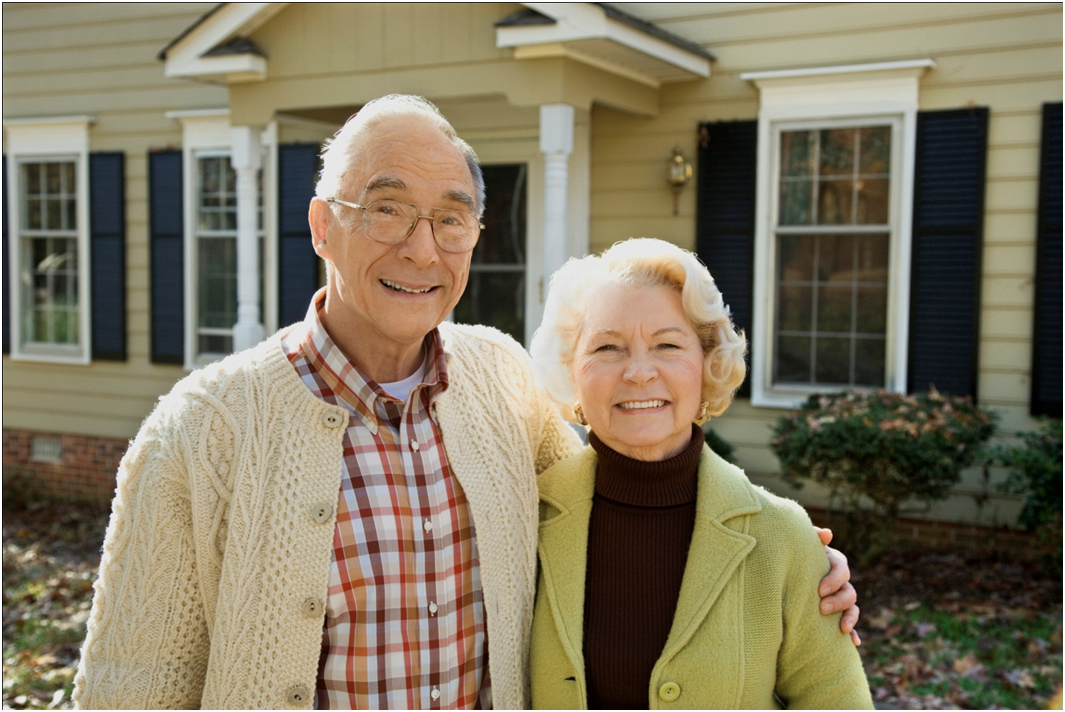 Senior Couple Standing in Front of Home